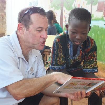 Voluntario mayor de 50 años enseñando a leer a un niño en Togo.